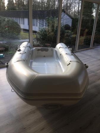 Rib boot met Suzuki motor, bolders, peddels, anker en een wit leren kussen